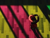 An aerial shot of a girl in a coat holding a cell phone up to her face. She's standing on a floor that's pink, yellow, and green from the lights shining down on it.
