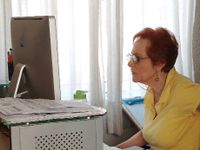 An older, red-headed woman with glasses and a yellow top is sitting in an office, looking at a computer screen.