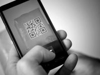 A black and white closeup of a hand holding a cell phone with a QR code on the screen.