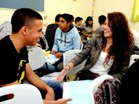 A closeup of two teenage students sitting in a classroom, talking, smiling, and laughing, with other kids sitting and talking in the background.