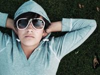 Boy in a hoodie wearing sunglasses laying on the grass