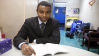 Boy in suit studying at a table
