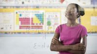 A girl looks confidently at a math problem on the board.