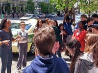 Class standing together on a street listening to instruction