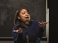 Girl expressively speaking in front of microphone