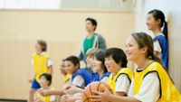 Students sitting on basketball court smiling