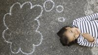 A smiling six-year-old girl lies on the school playground with a thought bubble drawn in chalk above her head.