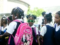 Group of students, many wearing backpacks, and one girl wearing neon green sunglasses