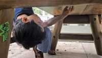 A boy looks under a table at school for a hidden game token.