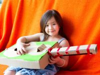 Young girl holding a cardboard guitar