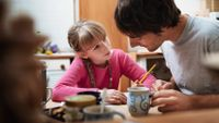 A man helping a girl with her homework the kitchen table