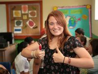 Girl in a classroom standing in front of students working giving two thumbs up