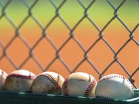 Photo of baseballs against a fence