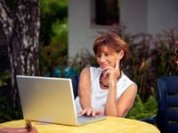 Woman with laptop sitting on a patio