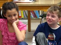 Girl and boy sitting on floor as part of circle, smiling