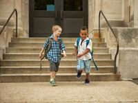 Two young boys wearing backpacks rushing down the front steps of school