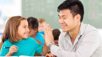 An elementary student and her teacher give each other a high-five at a table in a classroom.