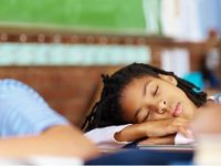 Girl sound asleep at her desk, arms crossed across her books