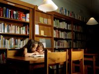 Two young girls huddled together reading a book in the library