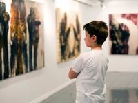 Boy in a museum looking at a painting