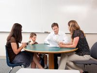 Mom, dad, and boy speaking with teacher around a table
