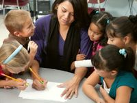 Teacher writing with a pencil surrounded by five young engaged students
