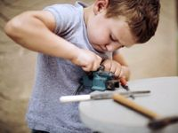Young boy determined to make something fit using a vice
