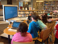 Photo of a group of students sitting around a computer lab table in the school library.