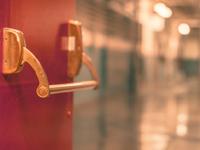 Photo of a door opening to an empty school hallway