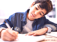 A photo of a middle school boy doing a writing assignment.