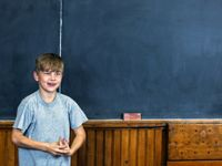 Boy speaking in front of blackboard