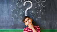 A young boy stands thinking in front of a blackboard covered with question marks.