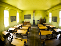 A fisheye photo of a classroom with wooden desks and a wood-burning stove.