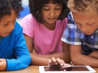 Three children around a tablet device