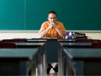 Man sitting at desk in an empty classroom