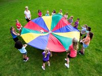 Teacher and students bouncing a ball on a parachute