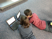 A photo of 2 elementary-school boys doing research on laptops.
