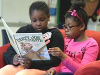 Two girls reading together