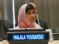 A young woman is sitting in front of two men, with a microphone by her mouth, and her name, Malala Yousafzai, displayed in front of her.