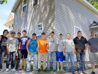 11 boys standing in front of a two-story house they have been renovating