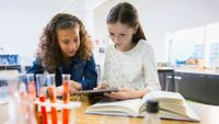 Two girls work together on a science project.