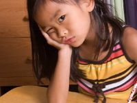 Young girl resting her head in her hand looking perplexed