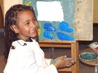 Young girl in smock in front of an easel with paint on her hands