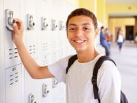 Boy at his locker outside hallway