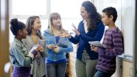 A teacher has a friendly chat with a small group of her students.