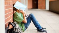 Middle school aged male student sitting with back to a wall holding an open book over his head and face.