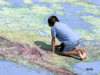 A photo of a young boy kneeling on a giant map of the world.