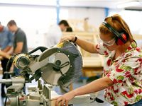 Girl operating a large table saw wearing safety headphones and goggles