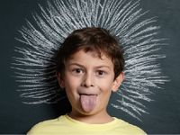 Boy with tongue out standing in front of chalk board drawing of big hair sticking up