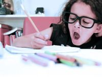 Young girl with glasses writing in a binder and yawning